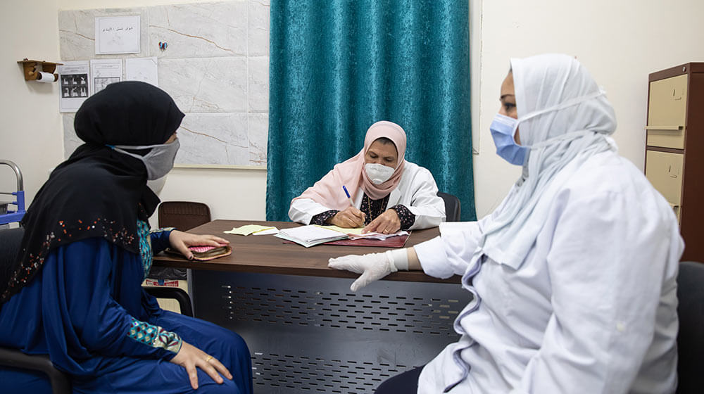 Masked woman receives a family planning consultation in Egypt.