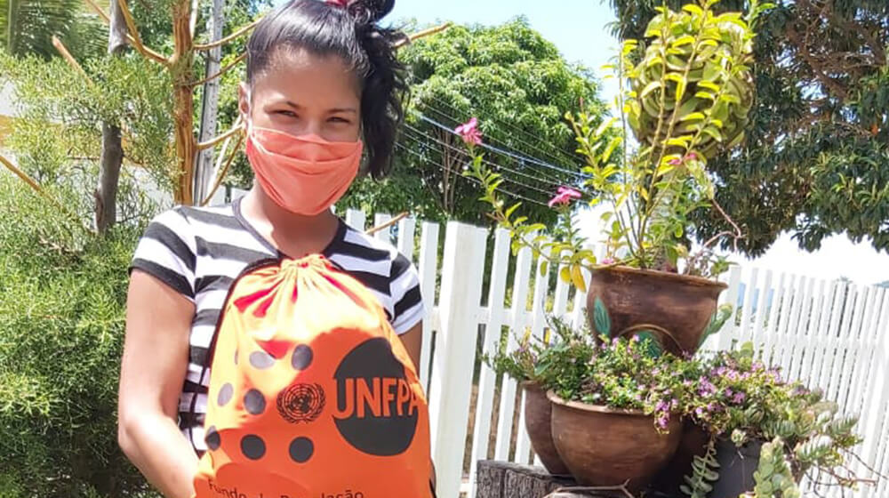 A pregnant woman with a UNFPA dignity kit wears a mask.
