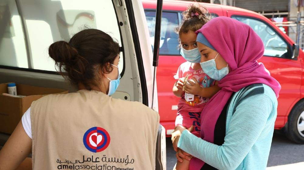 A health care worker with a mobile health clinic distributes dignity kits to women and girls.