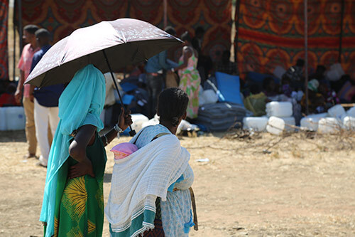 Two Ethiopian refugees huddle under an umbrella to escape the hot Sudanese sun.